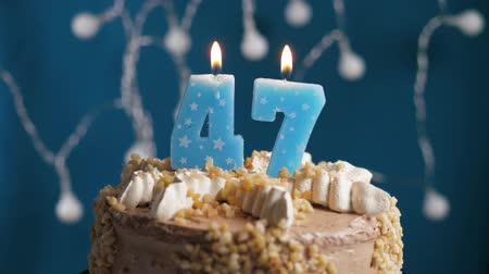 時代遅れの : Birthday cake with 47 number burning candle on blue backgraund. Candles blow out. Slow motion and close-up view