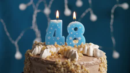 výrazný : Birthday cake with 48 number burning candle on blue backgraund. Candles blow out. Slow motion and close-up view