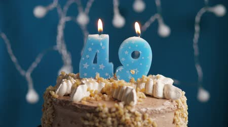 výrazný : Birthday cake with 49 number burning candle on blue backgraund. Candles blow out. Slow motion and close-up view