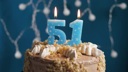 anlamlı : Birthday cake with 51 number burning candle on blue backgraund. Candles blow out. Slow motion and close-up view