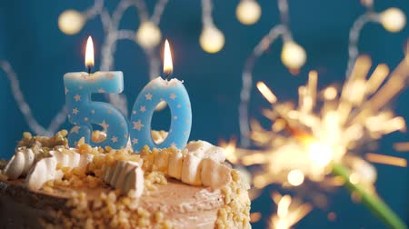 dígito : Birthday cake with 50 number candle and sparkler on blue backgraund. Slow motion and close-up view