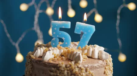 výrazný : Birthday cake with 57 number burning candle on blue backgraund. Candles blow out. Slow motion and close-up view