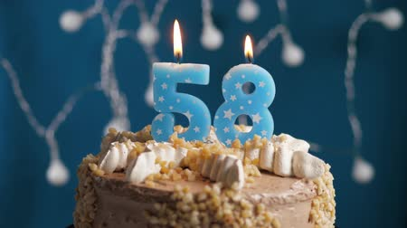 výrazný : Birthday cake with 58 number burning candle on blue backgraund. Candles blow out. Slow motion and close-up view