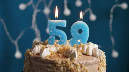anlamlı : Birthday cake with 59 number burning candle on blue backgraund. Candles blow out. Slow motion and close-up view Stok Video
