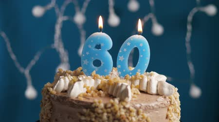 時代遅れの : Birthday cake with 60 number burning candle on blue backgraund. Candles blow out. Slow motion and close-up view 動画素材