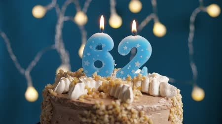 výrazný : Birthday cake with 62 number burning candle on blue backgraund. Candles blow out. Slow motion and close-up view