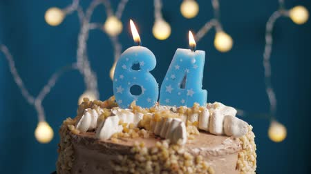 výrazný : Birthday cake with 64 number burning candle on blue backgraund. Candles blow out. Slow motion and close-up view