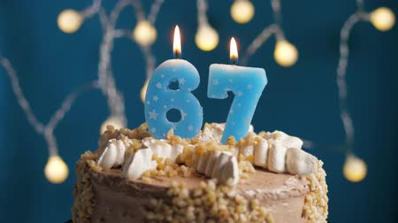 výrazný : Birthday cake with 67 number burning candle on blue backgraund. Candles blow out. Slow motion and close-up view