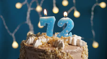 výrazný : Birthday cake with 72 number burning candle on blue backgraund. Candles blow out. Slow motion and close-up view