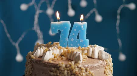 výrazný : Birthday cake with 74 number burning candle on blue backgraund. Candles blow out. Slow motion and close-up view