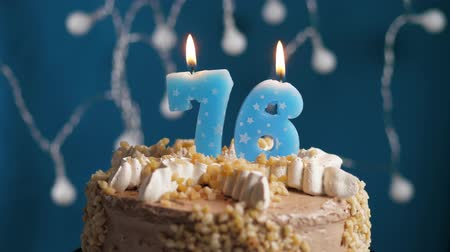 時代遅れの : Birthday cake with 76 number burning candle on blue backgraund. Candles blow out. Slow motion and close-up view 動画素材