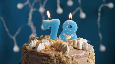 anlamlı : Birthday cake with 78 number burning candle on blue backgraund. Candles blow out. Slow motion and close-up view Stok Video
