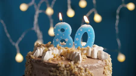 時代遅れの : Birthday cake with 80 number burning candle on blue backgraund. Candles blow out. Slow motion and close-up view