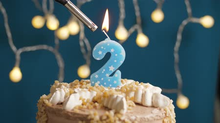 výrazný : Birthday cake with 2 number burning candle by lighter on blue backgraund. Candles are set on fire. Slow motion and close-up view