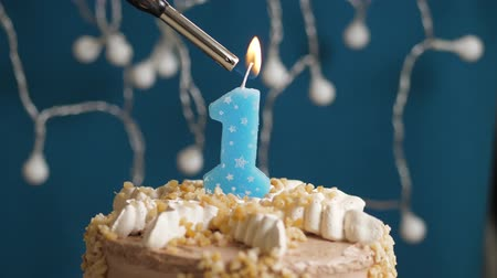 anlamlı : Birthday cake with 1 number burning candle by lighter on blue backgraund. Candles are set on fire. Slow motion and close-up view Stok Video