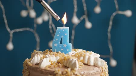 výrazný : Birthday cake with 4 number burning candle by lighter on blue backgraund. Candles are set on fire. Slow motion and close-up view