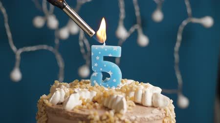 výrazný : Birthday cake with 5 number burning candle by lighter on blue backgraund. Candles are set on fire. Slow motion and close-up view Dostupné videozáznamy