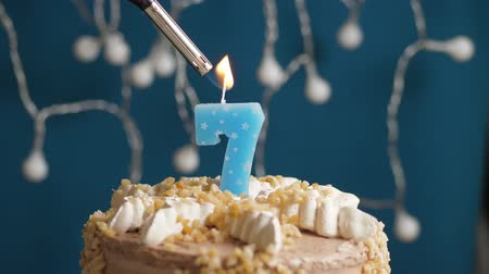 výrazný : Birthday cake with 7 number burning candle by lighter on blue backgraund. Candles are set on fire. Slow motion and close-up view