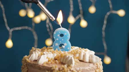 eight : Birthday cake with 8 number burning candle by lighter on blue backgraund. Candles are set on fire. Slow motion and close-up view Stock Footage