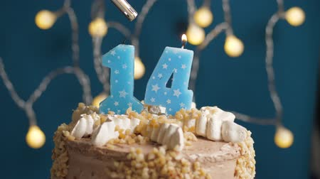 anlamlı : Birthday cake with 14 number burning candle by lighter on blue backgraund. Candles are set on fire. Slow motion and close-up view Stok Video