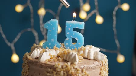 výrazný : Birthday cake with 15 number burning candle by lighter on blue backgraund. Candles are set on fire. Slow motion and close-up view Dostupné videozáznamy