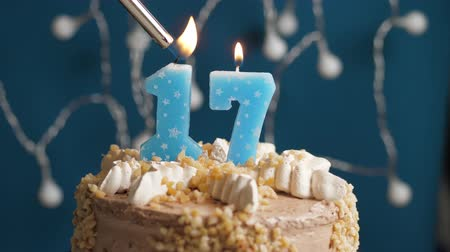 výrazný : Birthday cake with 17 number burning candle by lighter on blue backgraund. Candles are set on fire. Slow motion and close-up view