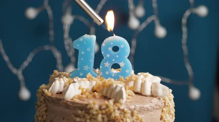 zapalovač : Birthday cake with 18 number burning candle by lighter on blue backgraund. Candles are set on fire. Slow motion and close-up view