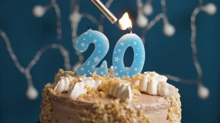 výrazný : Birthday cake with 20 number burning candle by lighter on blue backgraund. Candles are set on fire. Slow motion and close-up view