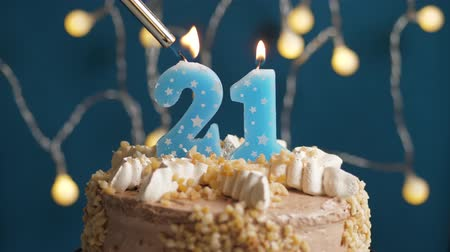 výrazný : Birthday cake with 21 number burning candle by lighter on blue backgraund. Candles are set on fire. Slow motion and close-up view