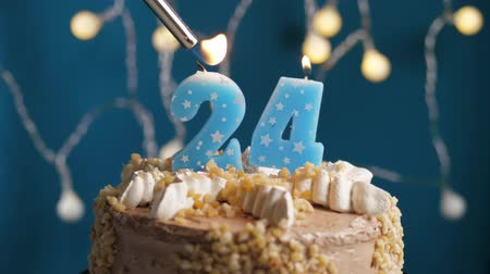 anlamlı : Birthday cake with 24 number burning candle by lighter on blue backgraund. Candles are set on fire. Slow motion and close-up view Stok Video