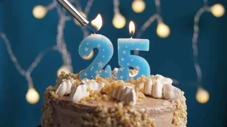 výrazný : Birthday cake with 25 number burning candle by lighter on blue backgraund. Candles are set on fire. Slow motion and close-up view Dostupné videozáznamy