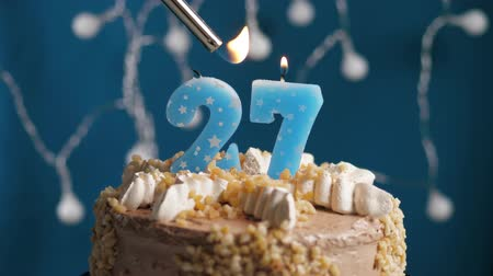 výrazný : Birthday cake with 27 number burning candle by lighter on blue backgraund. Candles are set on fire. Slow motion and close-up view