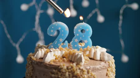 mechero : Birthday cake with 28 number burning candle by lighter on blue backgraund. Candles are set on fire. Slow motion and close-up view Archivo de Video