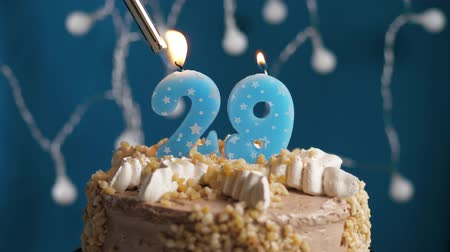výrazný : Birthday cake with 29 number burning candle by lighter on blue backgraund. Candles are set on fire. Slow motion and close-up view