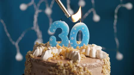 výrazný : Birthday cake with 30 number burning candle by lighter on blue backgraund. Candles are set on fire. Slow motion and close-up view