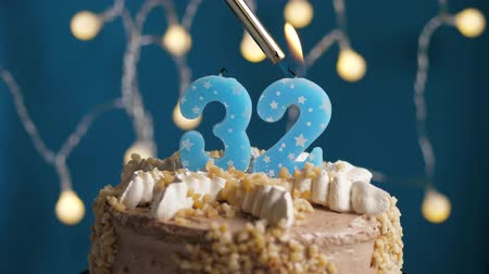 anlamlı : Birthday cake with 32 number burning candle by lighter on blue backgraund. Candles are set on fire. Slow motion and close-up view Stok Video