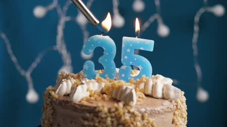 anlamlı : Birthday cake with 35 number burning candle by lighter on blue backgraund. Candles are set on fire. Slow motion and close-up view