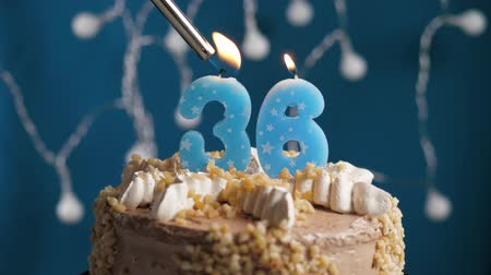 výrazný : Birthday cake with 36 number burning candle by lighter on blue backgraund. Candles are set on fire. Slow motion and close-up view Dostupné videozáznamy