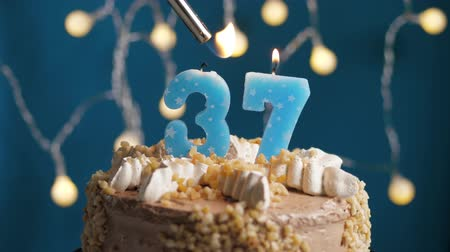 anlamlı : Birthday cake with 37 number burning candle by lighter on blue backgraund. Candles are set on fire. Slow motion and close-up view