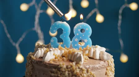 anlamlı : Birthday cake with 38 number burning candle by lighter on blue backgraund. Candles are set on fire. Slow motion and close-up view
