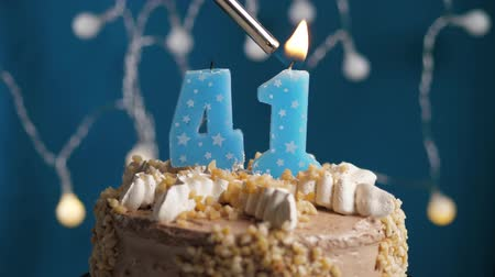 výrazný : Birthday cake with 41 number burning candle by lighter on blue backgraund. Candles are set on fire. Slow motion and close-up view