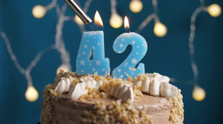 výrazný : Birthday cake with 42 number burning candle by lighter on blue backgraund. Candles are set on fire. Slow motion and close-up view