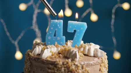 anlamlı : Birthday cake with 47 number burning candle by lighter on blue backgraund. Candles are set on fire. Slow motion and close-up view Stok Video