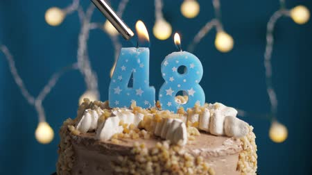 anlamlı : Birthday cake with 48 number burning candle by lighter on blue backgraund. Candles are set on fire. Slow motion and close-up view