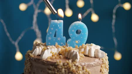 výrazný : Birthday cake with 49 number burning candle by lighter on blue backgraund. Candles are set on fire. Slow motion and close-up view