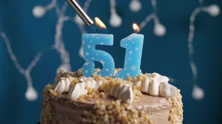 výrazný : Birthday cake with 51 number burning candle by lighter on blue backgraund. Candles are set on fire. Slow motion and close-up view