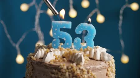anlamlı : Birthday cake with 53 number burning candle by lighter on blue backgraund. Candles are set on fire. Slow motion and close-up view