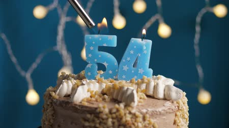 výrazný : Birthday cake with 54 number burning candle by lighter on blue backgraund. Candles are set on fire. Slow motion and close-up view
