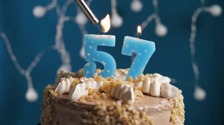 anlamlı : Birthday cake with 57 number burning candle by lighter on blue backgraund. Candles are set on fire. Slow motion and close-up view Stok Video