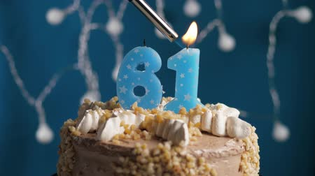 výrazný : Birthday cake with 61 number burning candle by lighter on blue backgraund. Candles are set on fire. Slow motion and close-up view Dostupné videozáznamy